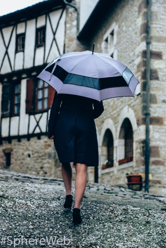 Sphère Web- Jeune femme au parapluie à Cordes sur ciel